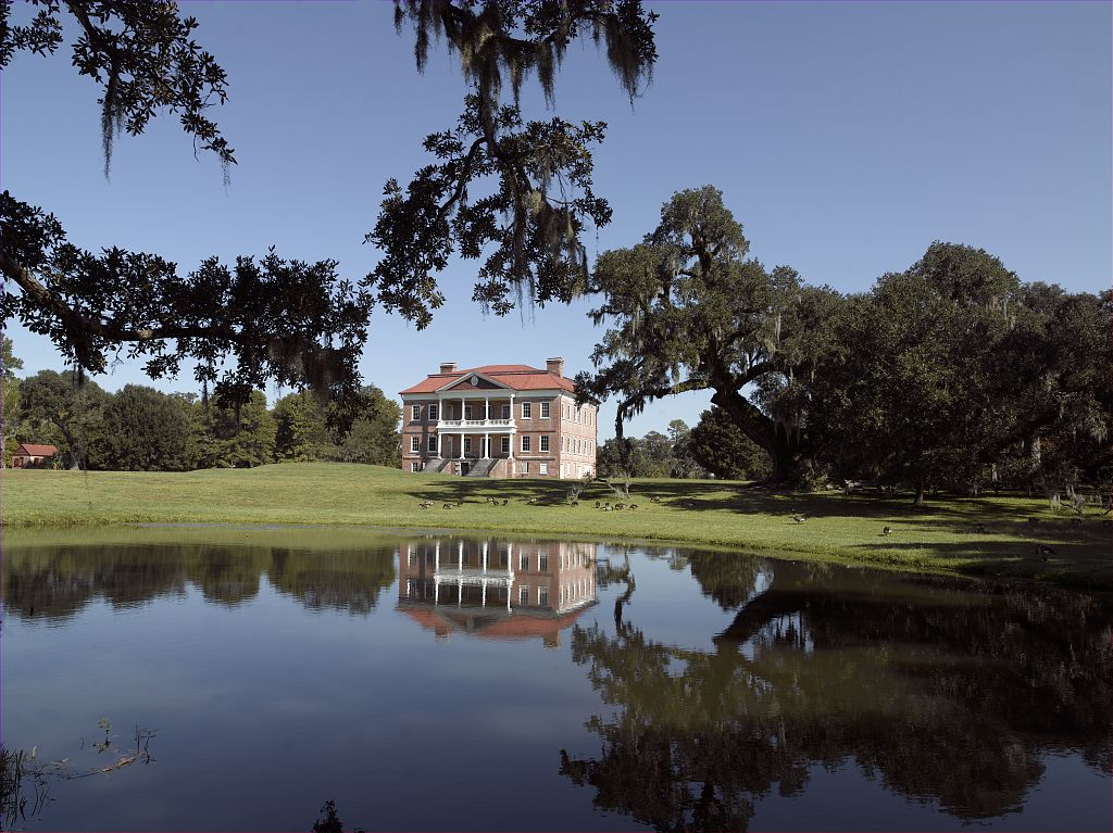 Drayton Hall, as seen behind some live oak trees from across the reflecting pond