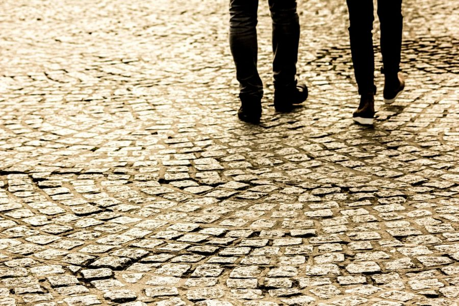 couple walking on a cobblestone street while taking one of the best charleston walking tours